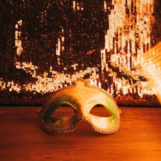 Masque de carnaval vert sur un bureau en bois avec des paillettes de paillettes d'or Photo gratuit