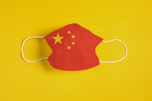 Masque Chirurgical Sur Fond Jaune Avec Le Drapeau De La Chine Photo gratuit