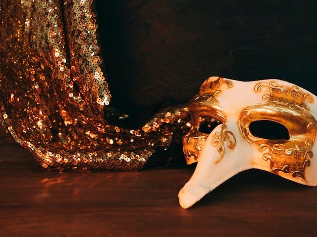 Masque de mascarade et textile paillettes d'or brillant sur le bureau en bois Photo gratuit