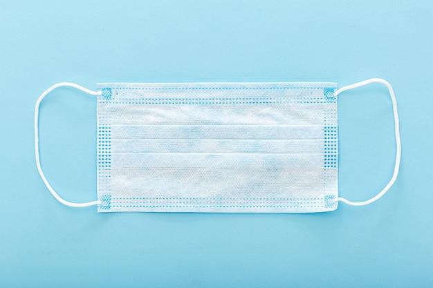 Masque Médical, Masque De Protection Médical Sur Fond Bleu. Le Masque Facial Chirurgical Jetable Couvre La Bouche Et Le Nez Pour Les Soins De Santé Photo Premium