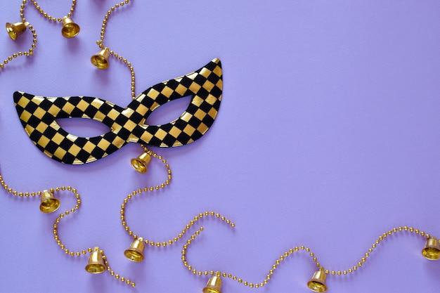 Masque Et Perles Avec Des Cloches Sur Fond Violet Sur Le Côté Gauche. Disposition à Plat Photo Premium