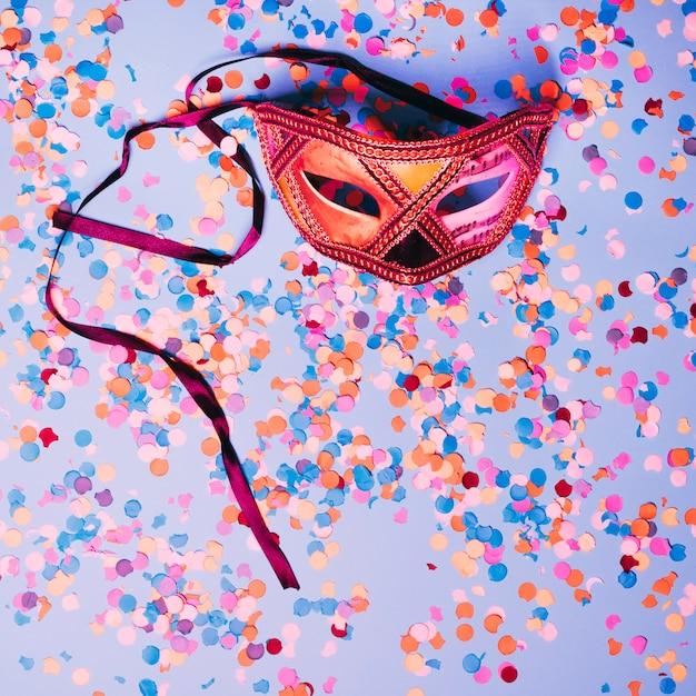 Masque pour les yeux carnival avec des confettis multicolores au-dessus de la toile de fond bleue Photo gratuit