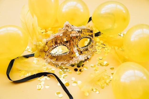 Masque près de ballons et de confettis Photo gratuit