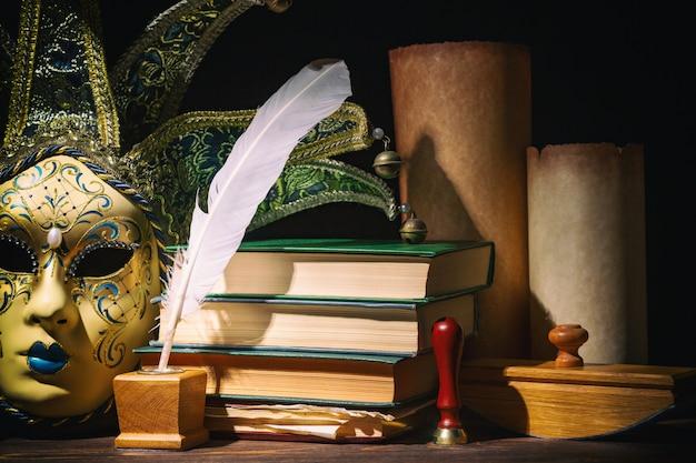 Masque Vénitien Avec Ancien Encrier, Plume, Plume, Rouleaux, Livres Et Sceau Sur Table En Bois. Photo Premium