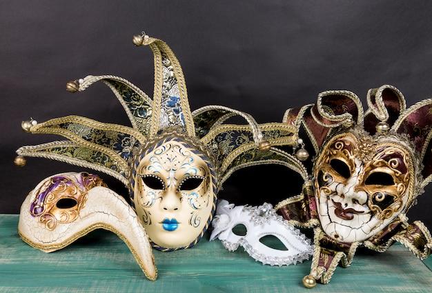 Masques De Carnaval De Venise Sur Une Surface En Bois Verte Sur Fond Sombre Photo Premium