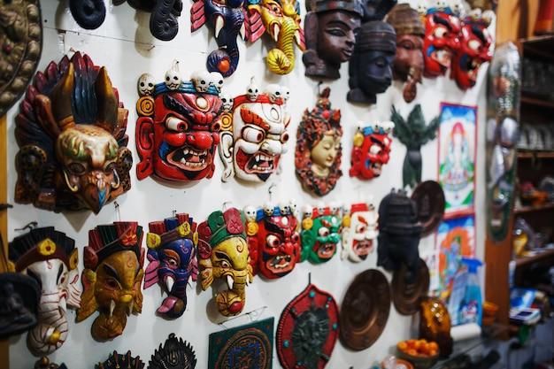 Des masques colorés sculptés sont vendus, des masques colorés de différents parfums sont accrochés au mur. Photo Premium