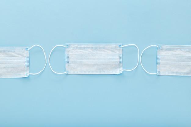 Masques De Protection Médicale Sur Fond Bleu. Un Masque Facial Chirurgical Jetable Couvre La Bouche Et Le Nez. Concept De Soins De Santé Photo Premium