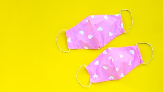 Masques En Tissu Rose Et Coeur Faits à La Main Sur Fond Jaune. Photo Premium