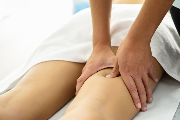 Massage médical à la jambe dans un centre de physiothérapie. Photo gratuit