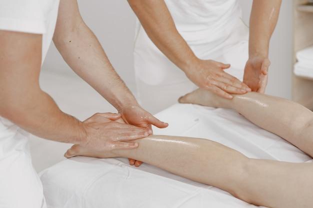Le Massage à Quatre Mains. Concept De Soins De Santé Et De Beauté Féminine. Deux Masseuses Font Un Double Massage D'une Fille. Femme Dans Un Salon De Spa. Photo gratuit