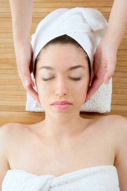 Massage visage belle femme avec une serviette blanche Photo Premium