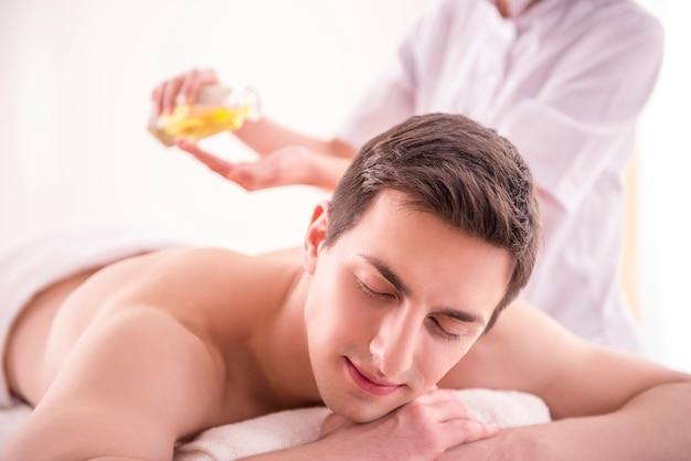Masseur fait un massage sur le corps de l'homme avec de l'huile de spa. Photo Premium