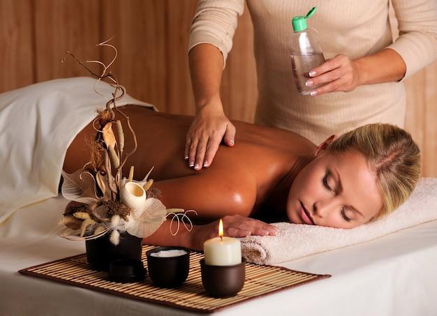 Masseur Professionnel Appliquant De L'huile De Massage Sur Le Dos Féminin Dans Le Salon De Beauté Photo gratuit