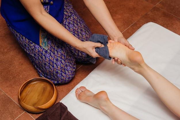 Un masseur thaïlandais en ostume asiatique fabrique des procédures de spa traditionnelles avec des jambes féminines. Photo Premium