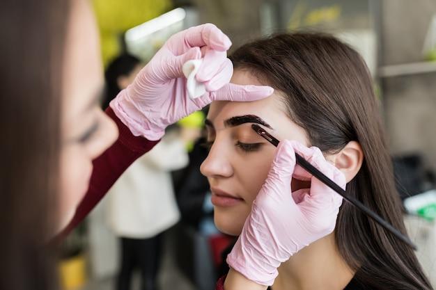 Master En Gants Blancs Travaillent à Balck Sourcils Dans Un Salon De Beauté Photo gratuit