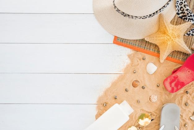 Mat avec chapeau et étoile de mer près des coquillages et de la lotion sur le sable Photo gratuit