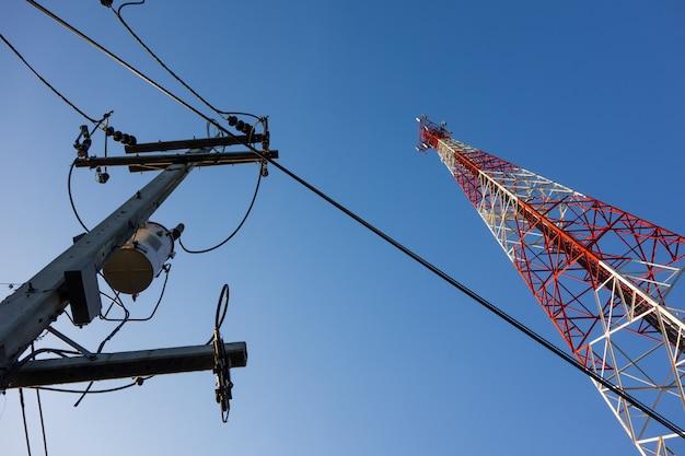 Mât rouge et blanc avec antennes de communication sur ciel bleu Photo Premium