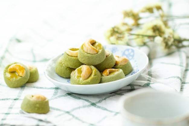 Matcha green tea cookies singapour ou noix de cajou au thé vert matcha cookies avec une tasse de thé chaud Photo Premium