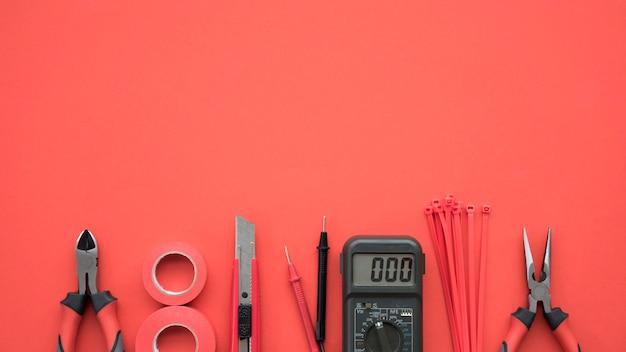 Matériel électrique disposé au bas du fond rouge Photo gratuit