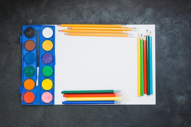 Matériel de peinture sur une feuille de papier blanc sur fond noir Photo gratuit