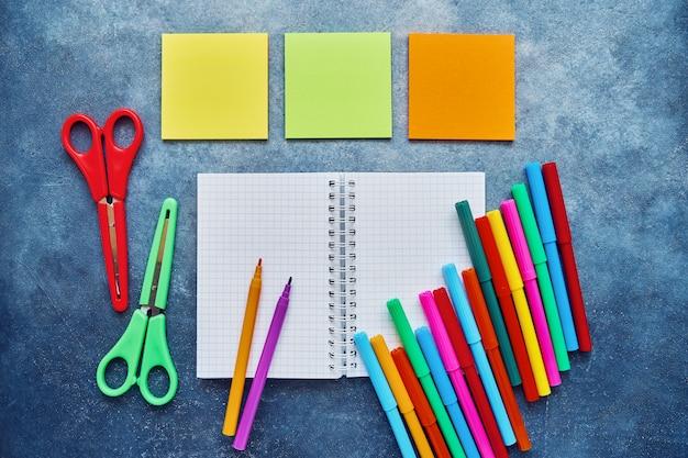 Matières scolaires sur un fond bleu foncé. retour au concept d'école. bloc-notes, bloc-notes, ciseaux de couleur et feutres. lay à plat, espace de copie Photo Premium