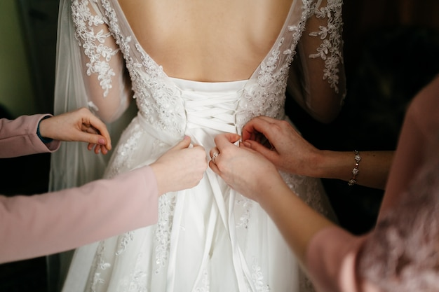 Matin de la mariée quand elle porte une belle robe Photo gratuit