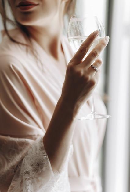 Le matin de la mariée. séduisante mariée boit du vin blanc debout befo Photo gratuit