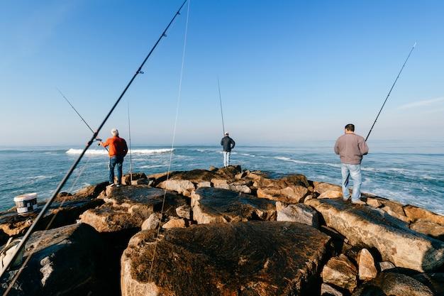 Matin à l'océan atlantique au portugal. groupe d'hommes adultes non reconnaissables pêchant. Photo Premium