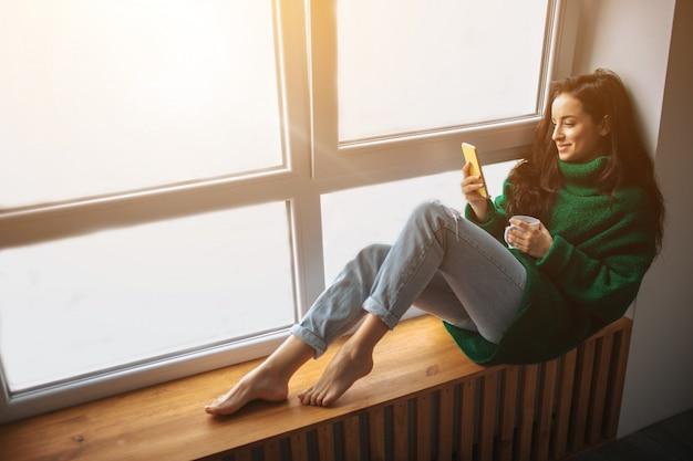 Matin Parfait Une Jeune Femme Brune Est Assise Sur Un Rebord De Fenêtre Et Tient Un Smartphone. Photo Premium