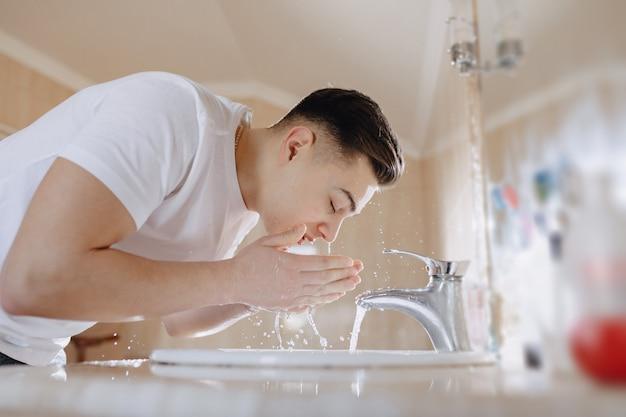 Matinée d'hygiène, le garçon est lavé dans un lavabo avec un jet d'eau Photo Premium