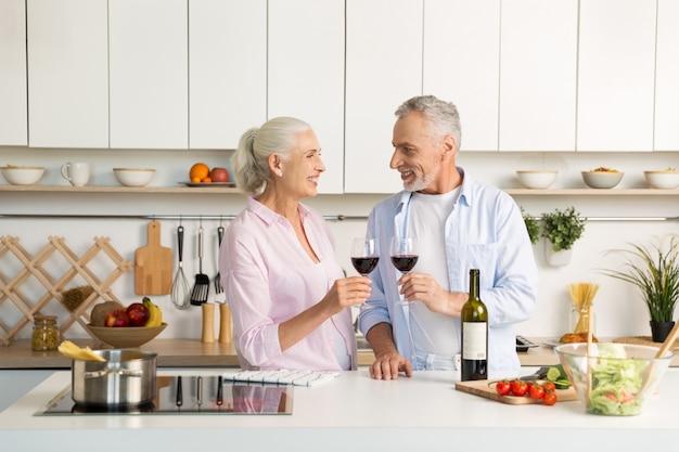 Mature Couple D'amoureux Heureux Debout à La Cuisine, Boire Du Vin Photo gratuit
