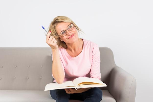 Mature femme assise sur un canapé tenant un stylo et un livre ouvert à la rêverie Photo gratuit