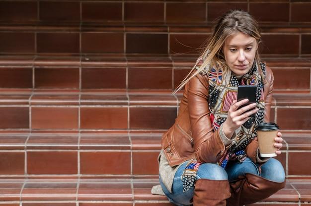 Mauvaise nouvelle. une jeune femme débarrassée avec un téléphone portable lit le message. Photo Premium