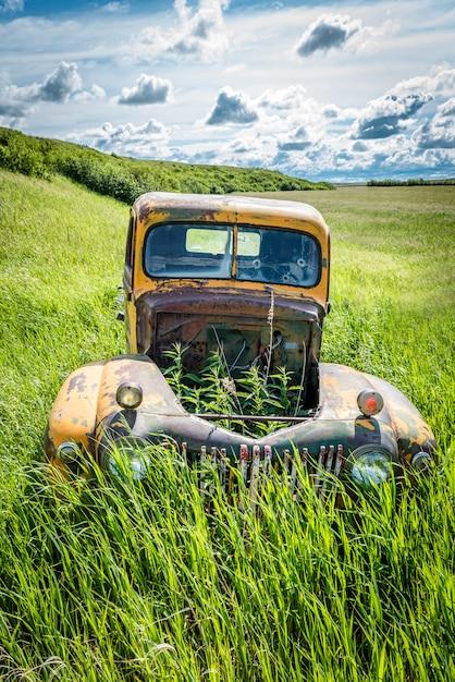 Les Mauvaises Herbes Grandissant à Travers Le Capot Vide D'un Camion Antique Abandonné Dans Les Hautes Herbes Photo Premium