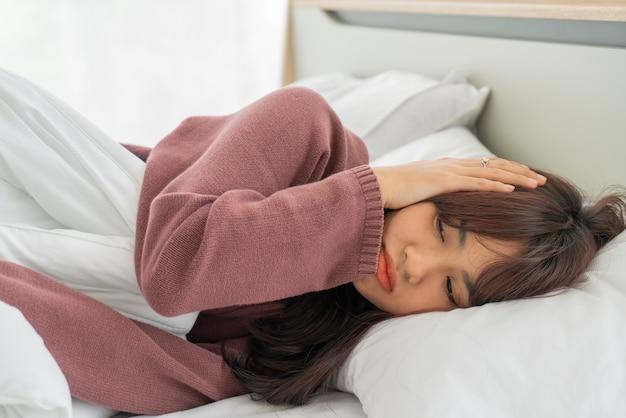 Maux De Tête De Femme Asiatique Et Dormir Sur Le Lit Photo Premium