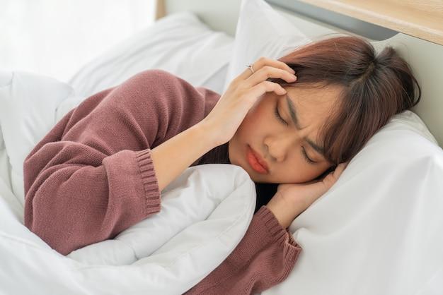 Maux De Tête Des Femmes Asiatiques Et Dormir Sur Le Lit Photo Premium