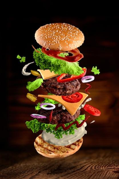 Maxi Hamburger, Double Cheeseburger Avec Des Ingrédients Volants Isolés Sur Bois Photo Premium