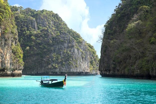 Maya bay en mer d'andaman et bateau en bois avec vue sur la montagne à phuket thaïlande Photo Premium