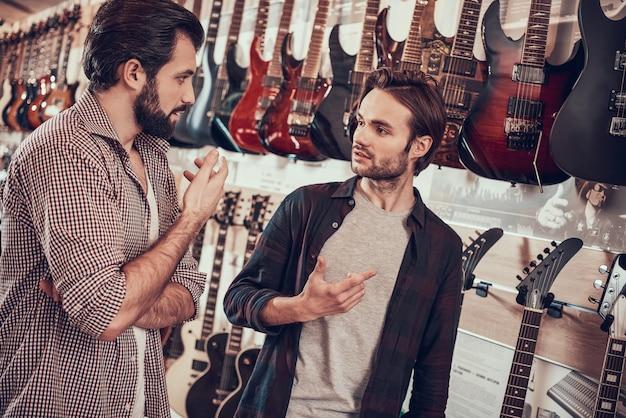 Un mec avec un arc montre comment tenir un violon dans un magasin de musique. Photo Premium