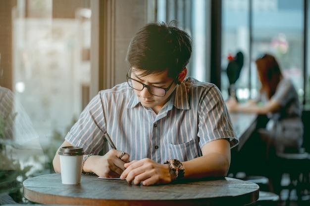 Mec asiatique avec des lunettes assis et écrit quelque chose avec pensée. Photo Premium