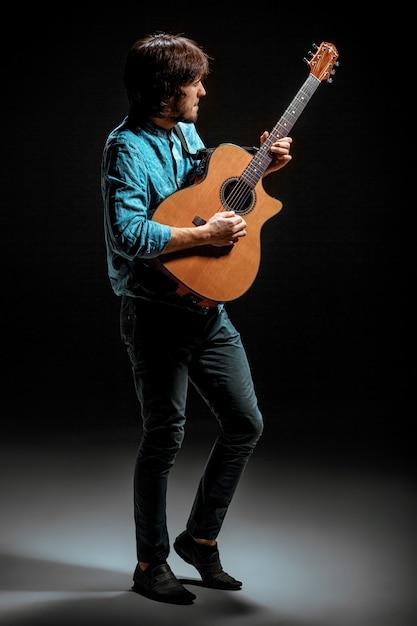 Mec Cool Debout Avec Guitare Sur Dark Photo gratuit