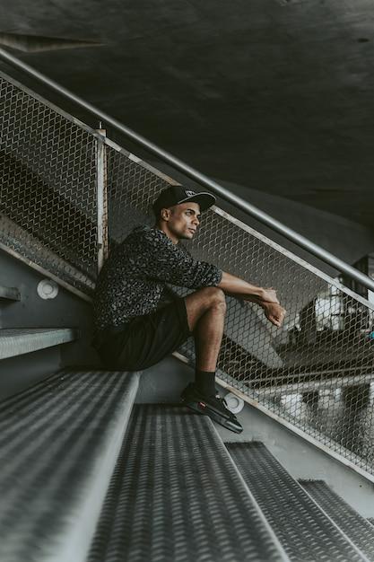 Mec élégant noir assis sur les stands Photo gratuit
