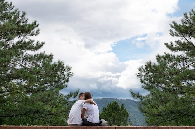 Le mec embrasse une fille au bord d'un grand immeuble sur fond de montagnes. Photo Premium