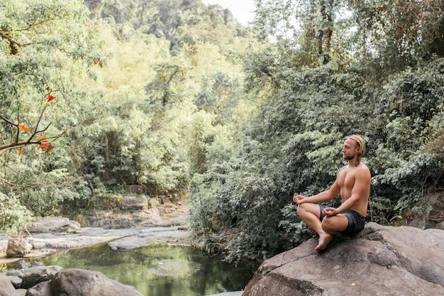 Le mec est en train de méditer sur une pierre dans la forêt Photo gratuit