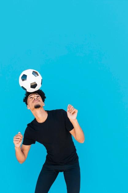Mec ethnique aux cheveux bouclés qui jouent avec le football Photo gratuit