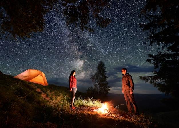 Un Mec Et Une Fille Se Font Face Et Tirent Entre Eux En Campant La Nuit Dans Les Montagnes. Photo Premium