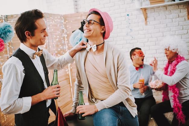 Mec gay touchant le noeud papillon d'un autre homme à la fête. Photo Premium