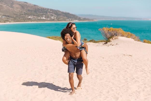 Mec heureux et souriant portant fille sur le dos sur la plage Photo gratuit