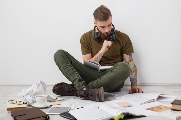 Mec Hipster Concentré Avec Des Tatouages, S'assoit Les Jambes Croisées Sur Le Sol, Lit Des Livres Et écrit Des Notes Photo gratuit