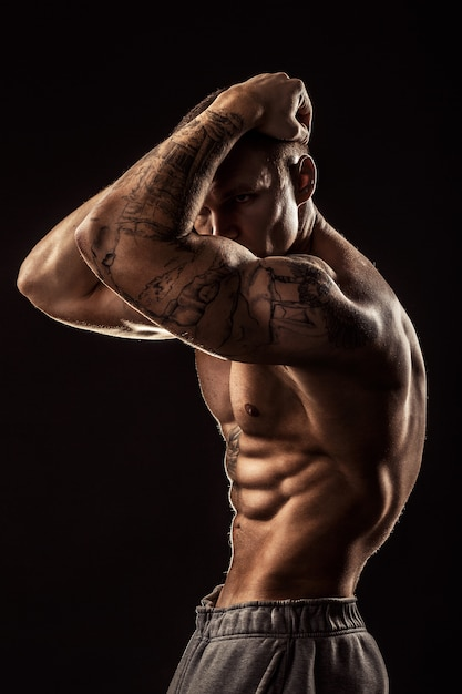 Mec musclé avec tatouage tenant sa tête. isolé sur fond gris Photo Premium